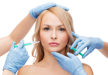 woman face and beautician hands with syringes