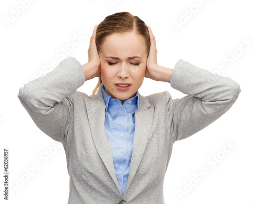 stressed businesswoman with covered ears