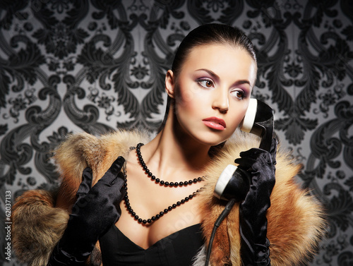 A beautiful woman with a retro telephone on a vintage background