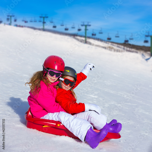 Kid girls playing sled in winter snow