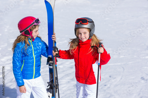 Kid girls sister in winter snow with ski equipment