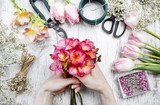 Fototapety Florist at work. Woman making bouquet of spring freesia flowers