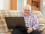 Happy man sitting on  couch with  laptop