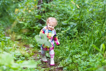 Cute curlu baby girl playing with big leaves in a park on a rain
