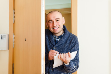 Happy man with papers near opens  door