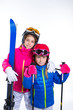 siters kid girls with ski poles helmet and snow goggles