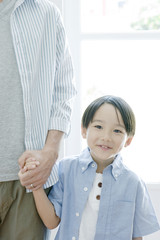 smiling boy holding hands with father