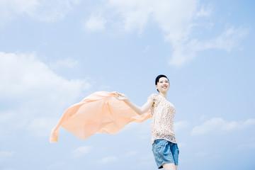 woman having cloth flutter under blue sky