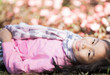 Little asian girl smile and resting on green grass