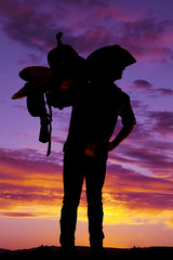 Silhouette of cowboy holding saddle on shoulder
