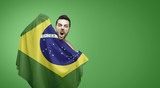 Brazilian fan holding the flag of Brazil celebrates on green