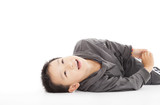 smiling  boy is lying  on the floor and looking up