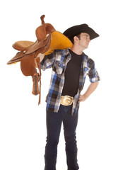 Cowboy holding saddle on shoulder look side