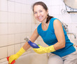 Mature woman cleans bathtub