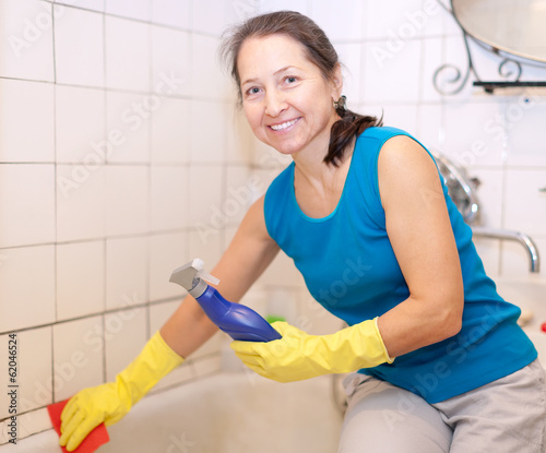 Mature woman cleans bathtub