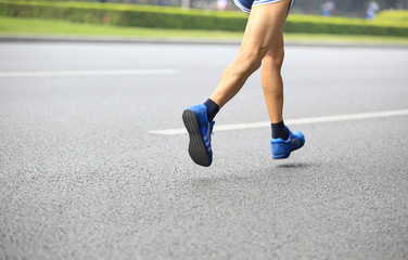 marathon runner legs running on street