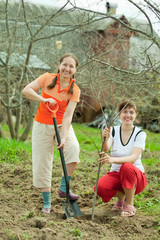 Happy women planting fruit tree