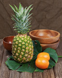 Still life with pineapple and oranges on wooden table.