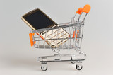 Cell phone in supermarket pushcart on gray background