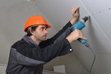 Man installing drywall using cordless drill