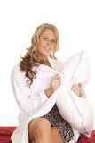 Woman white robe red sheet hold pillow smile