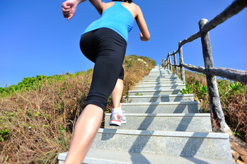 healthy young asian woman running up on mountain stairs to peak