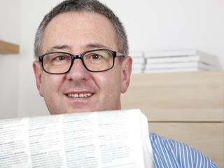 Man with glasses reading newspaper