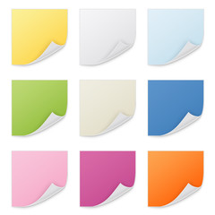 Color sticky notes thumbtacked to white background