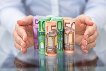 Hand Protecting Rolled Up Euro Banknote