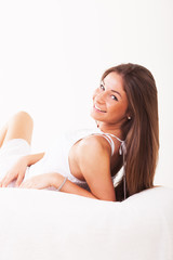 Beautiful young girl lying on bed and smiling.