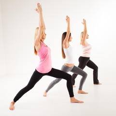 Three beautiful women doing Yoga Warrior I Pose.