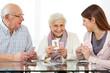 Senioren spielen Karten mit Sozialarbeiter