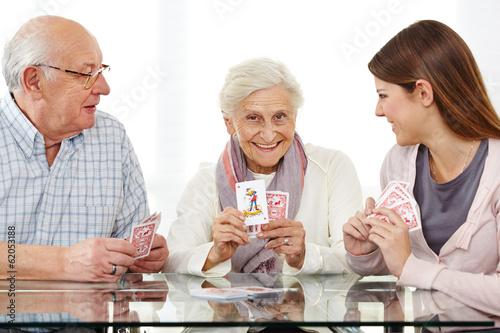 Leinwanddruck Bild Senioren spielen Karten mit Sozialarbeiter