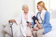 Krankenschwester misst Blutdruck bei Senioren