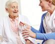 Seniorin nimmt Tablette mit Wasser