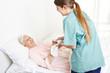 Leinwanddruck Bild - Krankenschwester wäscht eine bettlägerige Seniorin
