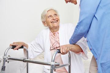 Krankenschwester hilft einer Seniorin beim Aufstehen