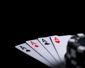 four aces on black table with chips