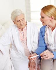 Krankenpflegerin mit Fieberthermometer