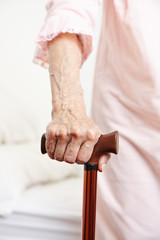 Hand einer Seniorin mit Gehstock