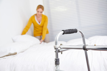 Putzfrau macht Bett im Seniorenheim