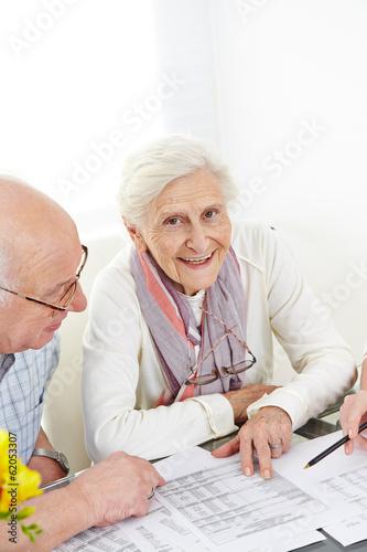Leinwanddruck Bild Zwei Senioren planen Versicherung und Steuern