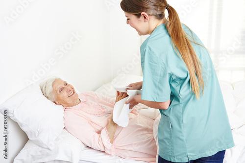 Leinwanddruck Bild Krankenschwester wäscht eine bettlägerige Seniorin
