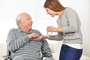 Frau gibt Mann im Rollstuhl Medikamente