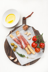 Prosciutto ham grisiini breadsticks with olive oil and tomatoes