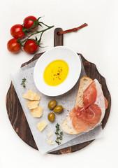 Prosciutto ham, ciabatta and parmesan cheese on a cutting board