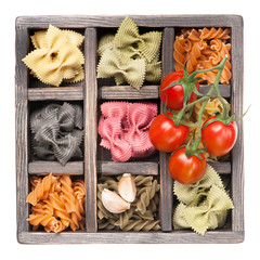 Mix Italian pasta, cherry tomatoes, garlic in vintage wooden box
