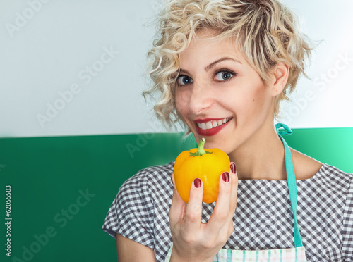 Young smiling woman cook holding pepper