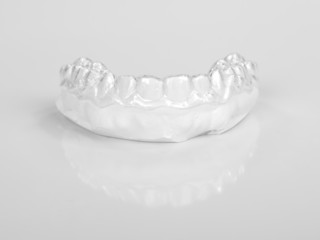 Translucent upper essix retainer on a gray background