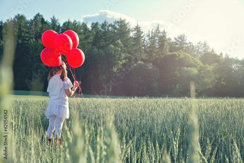 Girl with a bunch of red balloons